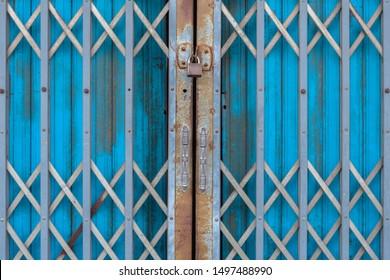 Vintage blue painted steel sliding door with safety key lock.