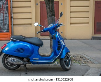 Vintage blue scooter is on the street.