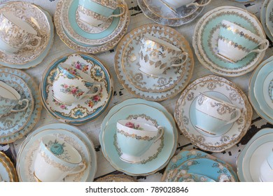 Vintage blue tea cups and saucers on a distressed wood table high tea party
