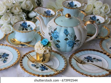 Vintage blue teacup, saucer, plate and teapot, iced cupcake with blue rose topper, gold cake fork, high tea party