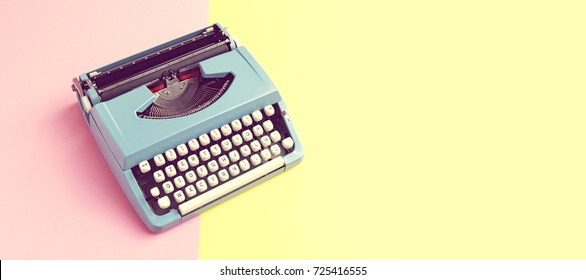 Vintage blue typewriter over a pastel background with space for copy