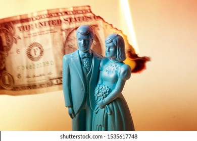 Vintage blue wedding cake topper couple in front of a dollar bill on fire. Weddings can be costly and a waste of money. Couple fighting over finances. Man and wife in financial trouble or divorce.