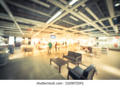 Vintage blurred customer shopping for dining table chair set in large furniture warehouse. Defocused motion home accessories store in America.