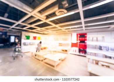 Vintage blurred customer shopping for living room supplies at huge furniture store in USA. Sofa, chairs, recliner, coffee/sofa table, ottoman display at interior showroom. Home furnishings concept
