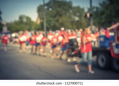 Vintage blurred Fourth of July parade celebration in Irving, Texas, USA. Residents enjoy walking in groups, decorating floats vehicle and celebrate the nation founding with family and friends