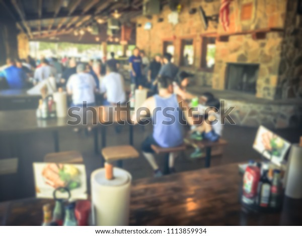Vintage blurred people having lunch on patio picnic table of BBQ restaurant. Open space Texas-style barbecue in a rustic, cafeteria-style setup in Coppell, Texas, USA