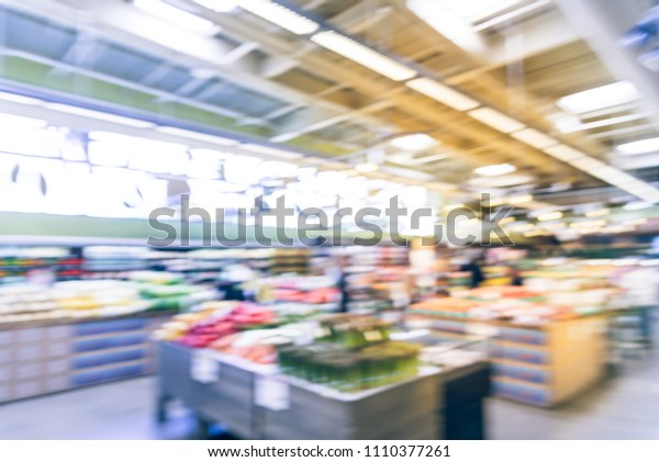 Vintage blurred people shopping for fresh fruits and vegetables at grocery store. Organic and locally grown produces on display in Allen, Texas, USA. Healthy food abstract background in supermarket