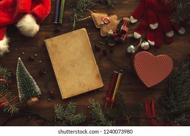 Vintage book among Christmas decoration, flat lay top view, nostalgic retro toned image