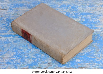 Vintage book in gray binding on a blue background. View from above.