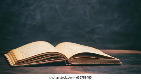 Vintage book on blackboard background - copy space