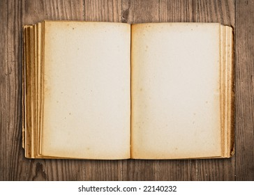 Vintage book, open, on old wooden table, with clipping path.