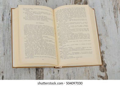 Vintage book, open, on old wooden table