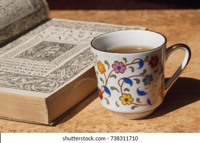 Vintage book with poems printed at 18th century on table with old fashion designed cup of coffee. Selective focus.