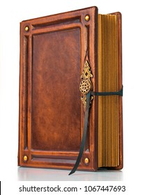 Vintage book in warm brown leather with gilded paper edges and metal buckle stand up to the table
