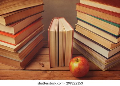 Vintage books with apple on wooden table. Reading a lot of books concept