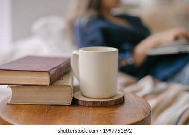 Vintage books with coffee cup or mug on wooden table against the background of a girl working at a laptop. Place for text, design. mockup. Selective focus