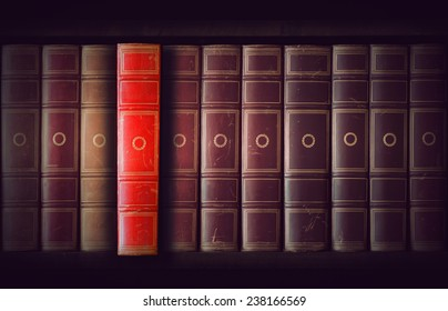Vintage books in different shades of red and brown in bookcase, one book slightly pulled out