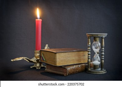 Vintage books and hourglass on dark background with firing red candle