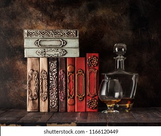Vintage books on a shelf and cognac in a glass and a bottle