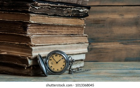 Vintage books and pocket watch on a wooden desk
