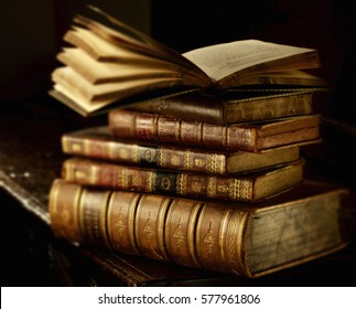 Vintage books stack on old wooden surface in warm directional light. Selective focus.