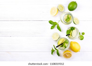 Vintage bottle with two glasses of refreshing non alcoholic mojito lemonade, sparkling water drink with lemon, lime slices, mint leaves, straw, wooden table background. Close up, top view, copy space.