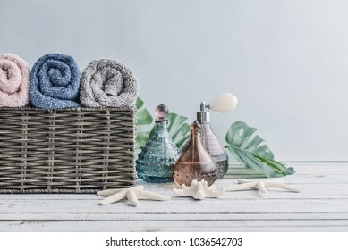 Vintage bottles with towels in a wicker basket on a light background