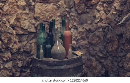 vintage bottles of wine in the old wine-rack from the underground wine cellar for winery storage where winemaker keeps the wine production in the wineyard chateau wine vault