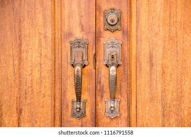 Vintage brass door handle with lock on wooden door