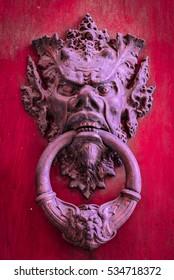Vintage brass door knob on red wooden background.