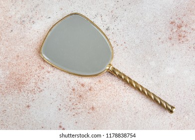 Vintage brass hand mirror on concrete background. Copy space for text.