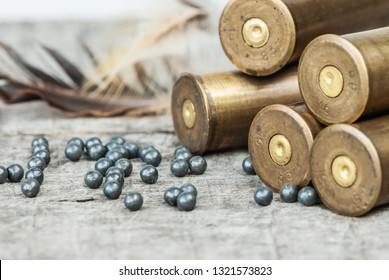 Vintage brass hunting cartridges and large lead shot on an old wooden background close-up