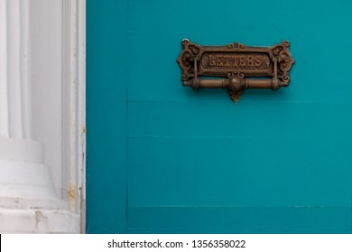 A vintage brass letter mail slot and door knocker. The door is a teal blue color with a white pillar and door frame. The old worn metal plate has the word letters on the front.