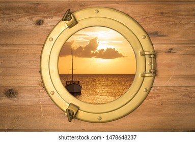 Vintage brass porthole in rustic wooden wall with view to a boat in sunset