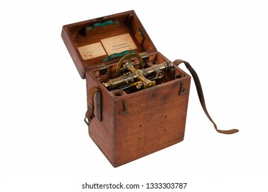 Vintage Brass Surveying Level (Transit, Theodolite) with Compass and natural aged Brass Patina, in its Wood Storage Box isolated on a white background.