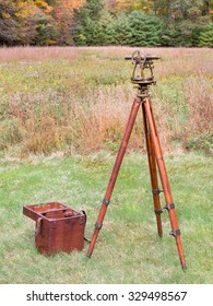 Vintage Brass Surveying Level (Transit, Theodolite) with Compass and aged Brass Patina, on a  wooden Tripod with Storage Case in a field.