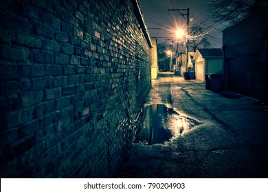 Vintage brick wall in a dark, gritty and wet Chicago alley at night after rain.