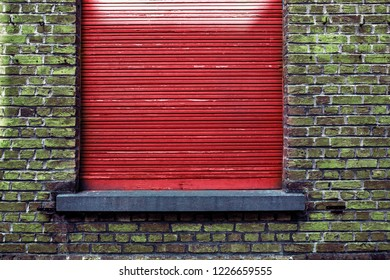 Vintage brick wall with red roller blinds.