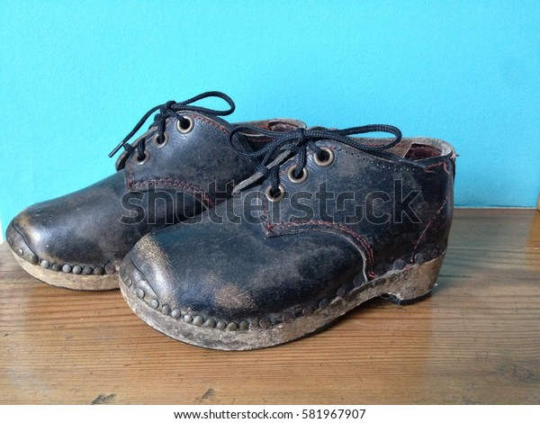 Vintage British children's clogs, leather lace up with wooden soles and clog irons, side and under sole view, foot wear