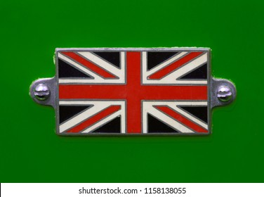 A Vintage British Union Jack flag badge on a racing green coloured car in close up