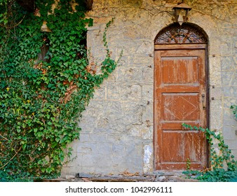 vintage brown arched door on stone wall and ivy foliage