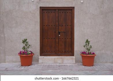 a vintage brown door with two pots