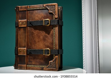Vintage brown leather book with two straps stay up on rounded white table, captured in front of green wall and the mirror