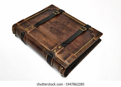 Vintage brown leather photo album with belts lay down to the table and captured isolated