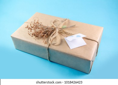 Vintage Brown Paper Wrapped Present Box with Dried Flowers and Tag on Blue Background