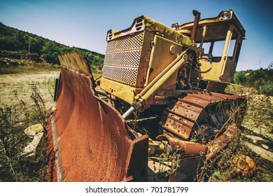 Vintage bulldozer. An abandoned old tractor with a bucket on a stone quarry. Old tractor in the field
