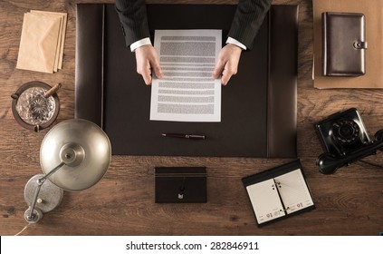 Vintage businessman in the office reading a contract sitting at his desk, top view