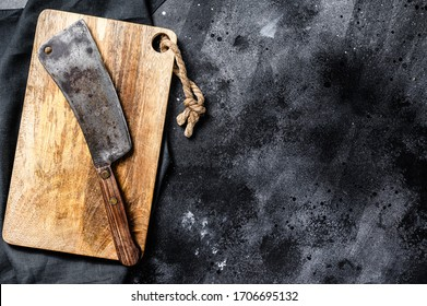 Vintage butcher meat cleaver on concrete board. Black background. Top view. Copy space