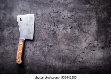 Vintage butcher meat on dark concrete board.