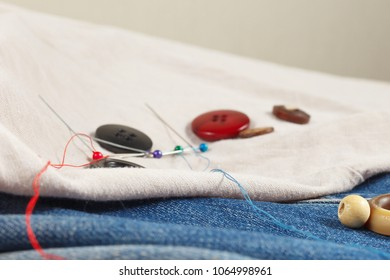 Vintage buttons, pins and needles with threads on canvas and denim close up